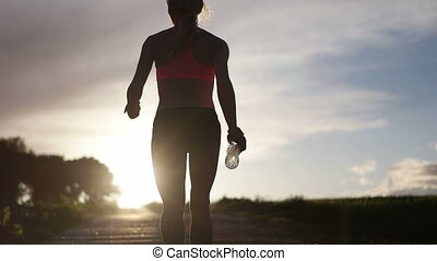 Woman running with water bottle - Video of a young blonde...
