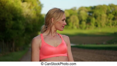 Woman In Sports Bra Walking - Video of a young blonde woman...