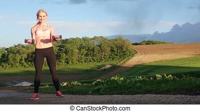 Blonde Woman Using Dumbells