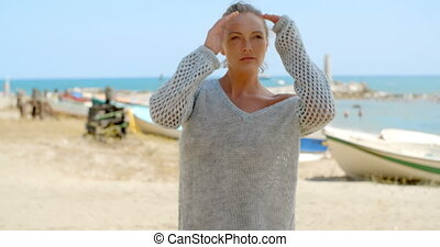 Woman in Grey Sweater on Beach Looking at Ocean - Blond...