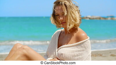Blond Woman Sitting on Beach in front of Ocean - Head and...