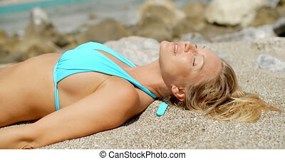 Blond Woman Wearing Bikini Lying on Sandy Beach - Smiling...