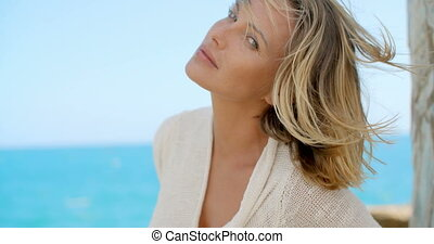 Blond Woman with Wind Swept Hair in front of Ocean - Head...