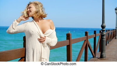 Blond Woman Wearing Light Sweater on Windy Pier - Blond...