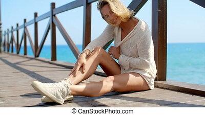 Blond Woman Wearing White Sweater on Ocean Pier - Blond...