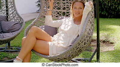 Woman Relaxing in Wicker Chair Outdoors in Garden - Blond...