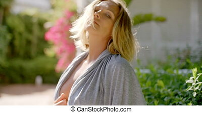 Blond Woman Wearing Open Grey Robe in Garden - Blond Woman...