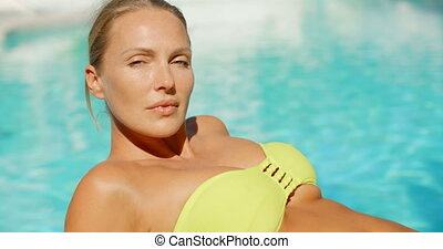 Woman in Yellow Bikini Suntanning Beside Pool - Blond Woman...