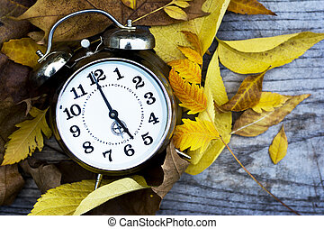 Retro clock on a wooden table with autumn leaves - Retro...
