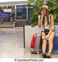 Young girl with a suitcase and papers sitting on the...