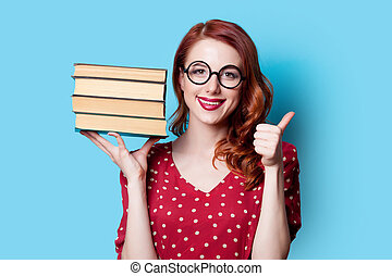 girl in red dress with books - Young smiling redhead teacher...
