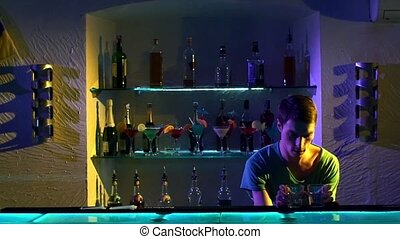 Young bartender making tricks with two glasses and bottle...