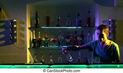Young barman making tricks with two glasses and bottle...