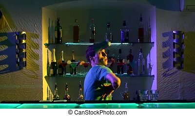 Young bartender making professional tricks with two glasses,...