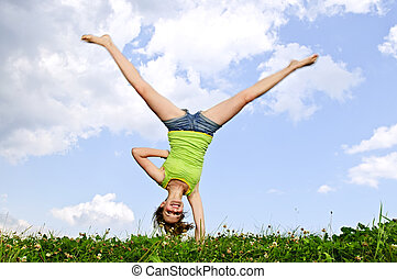 Young girl doing cartwheel - Young teenage girl doing...