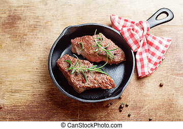 Steaks on cast iron frying pan Rustic background