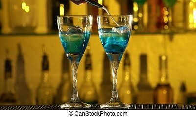 Barman puts cubes of ice into a glass, pouring three different alcohol liquids, turquoise, using gayser, two glasses, bar, spatter, slow motion
