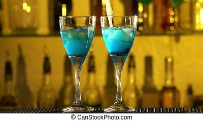 Barman puts cubes of ice into a glass, pouring three different alcohol liquids, turquoise, using gayser bar, two glasses bar, spatter, slow motion