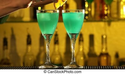 Barman puts cubes of ice into a glass, pouring three different alcohol liquids, turquoise, using gayser, two glasses, decorates with slice of orange and cherry, bar, spatter, slow motion