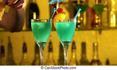 Barman puts cubes of ice into a glass, pouring three different alcohol liquids, turquoise, using gayser, two glasses, decorates with slice of orange and cherry, tubules, bar, spatter, slow motion