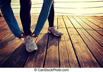 woman runner tying shoelace on wooden boardwalk sunrise...