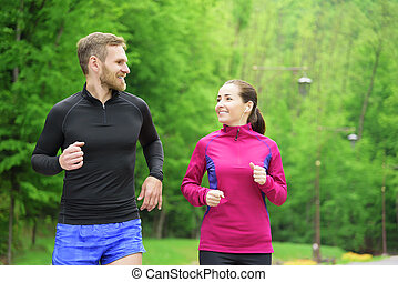 Couple running in park. - Attractive caucasian couple...