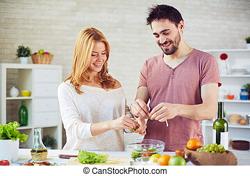 Cooking together - Amorous young couple cooking salad...