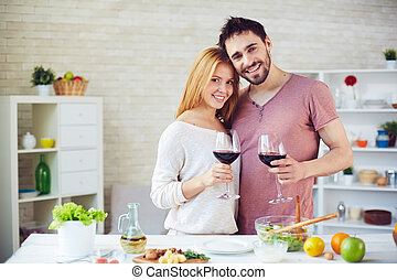 Toasting with red wine - Young man and woman with red wine...