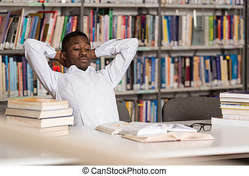 Confused Male Student Reading Many Books For Exam - Stressed...