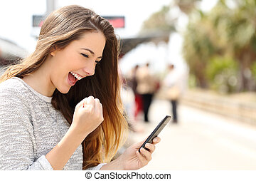 Euphoric woman watching her smart phone in a train station...