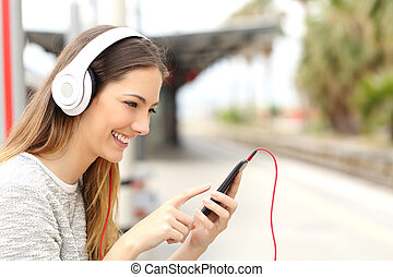 Teen girl listening to the music with headphones waiting a...