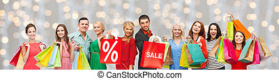 happy people with sale sign on shopping bags - consumerism,...