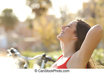 Woman breathing fresh air and relaxing - Back light of a...