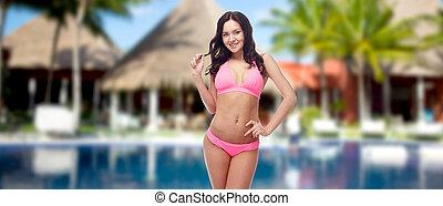 happy young woman in pink bikini swimsuit on beach - people,...