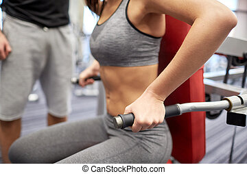 close up of woman flexing muscles on gym machine