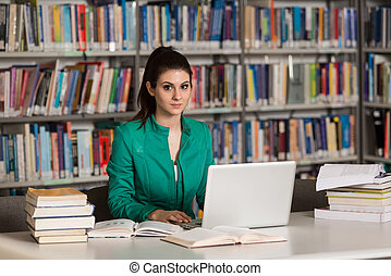 Happy Female Student With Laptop In Library