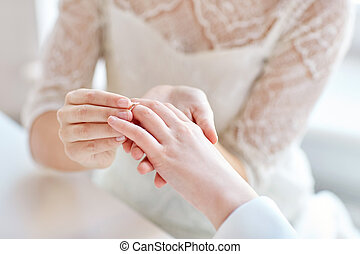 close up of lesbian couple hands with wedding ring - people,...
