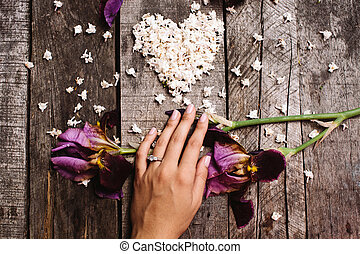 heart shape of white lilac flowers and hand with ring on...
