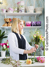Female looks critically at her boquet - A female florist...