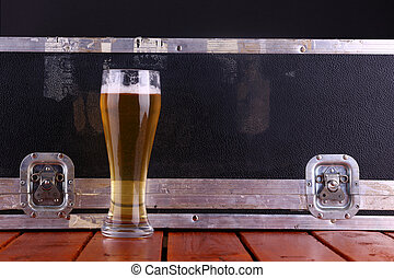 Beer and crate - Tall glass full of light beer standing on a...