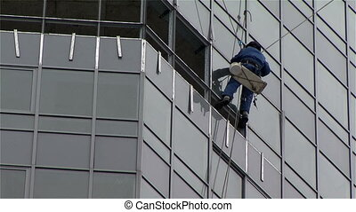 Worker washing windows multistory building hd