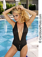 The very beautiful woman is standing in the sexy black swimsuit at the swimming pool
