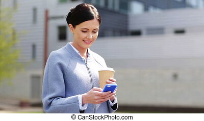 smiling woman with coffee cup and smartphone - business,...