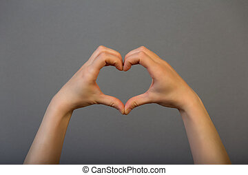 Hands heart symbol on grey background, close up