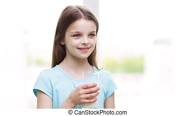 happy smiling little girl drinking milk at home
