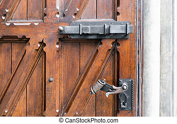 Wooden vintage door with wrought-iron locks and bars -...