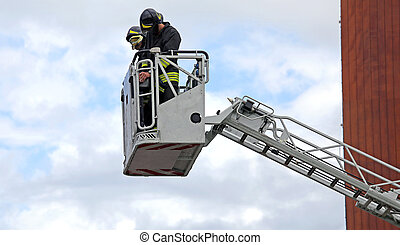 firefighters in the fire truck basket during the practice of...