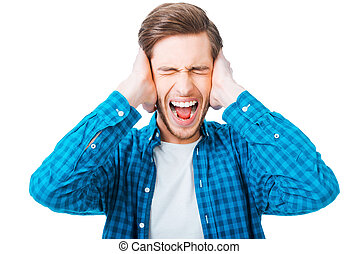 This is too loud! Frustrated young man holding head in hands...