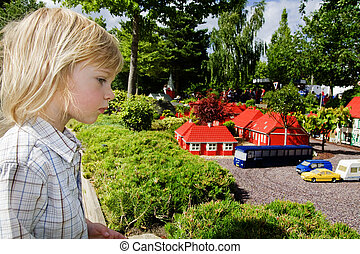 Child theme park legoland - child in looking at lego models....
