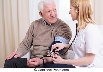 Caregiver checking the hypertension - Young smiling...